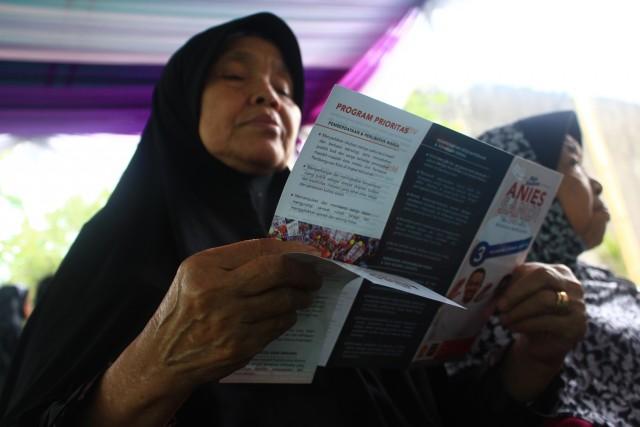 Salah satu peserta Baksos Anies-Sandi menunggu antrian Pelayanan Kesehatan dengan membaca brosur program-program Anies-Sandi. Ika